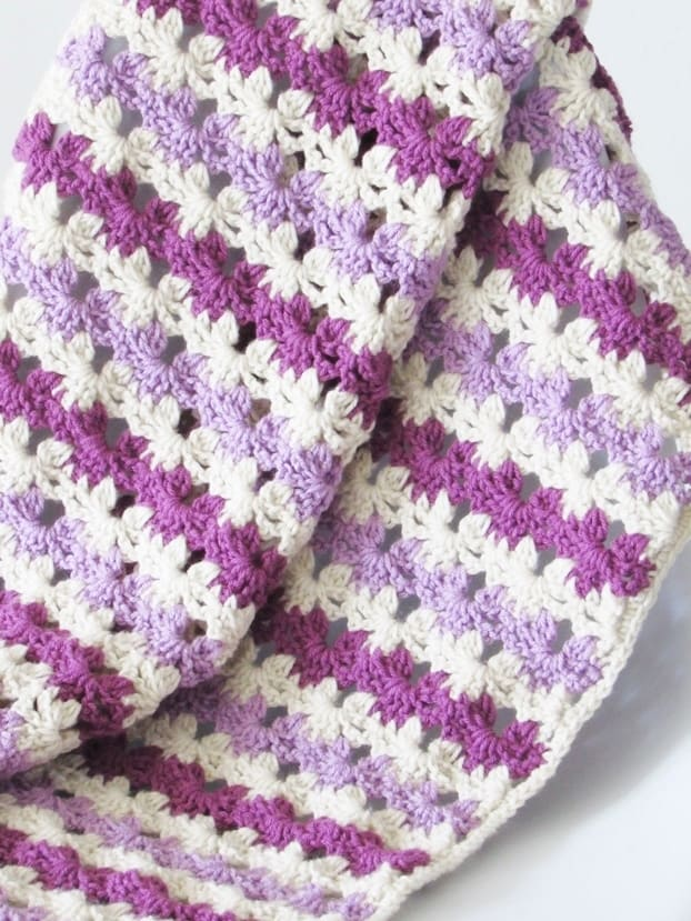 You will love this crochet blanket pattern that works up quickly and looks like rows of flowers.